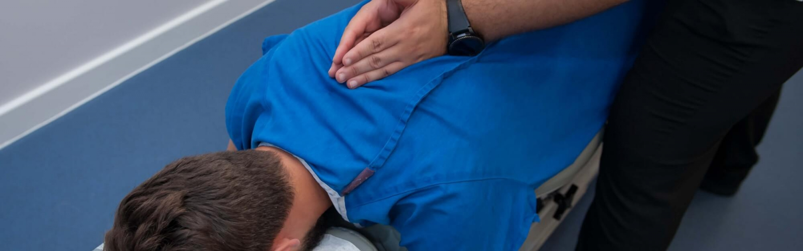 A male chiropractor treating a male patients back